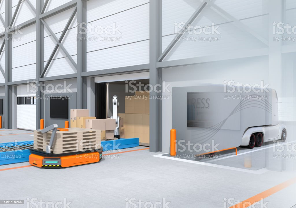 Industrial robot unloading parcels from semi truck, Automatic Guided Vehicle carrying set of pallets to the robot position stock photo