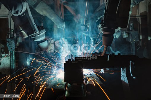 693576566 istock photo Industrial robots are movement welding automotive part in factory 966210030