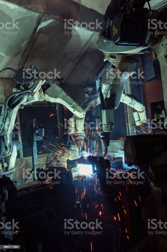 Industrial robots are movement welding automotive part in production...