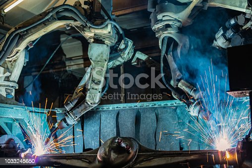693576566 istock photo Industrial robots are welding automotive part 1033245650