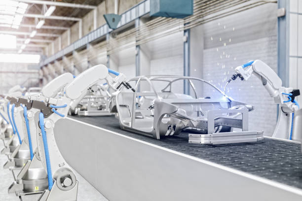industrial robots at the automatic car manufacturing factory assembly line - automatizzato foto e immagini stock