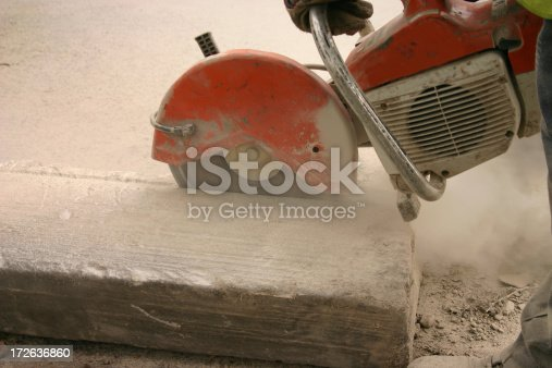detailed shot of a petrol saw cutting a large kerb