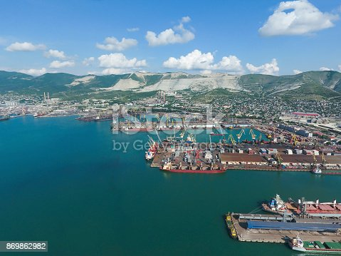 istock Industrial seaport, top view. Port cranes and cargo ships and ba 869862982