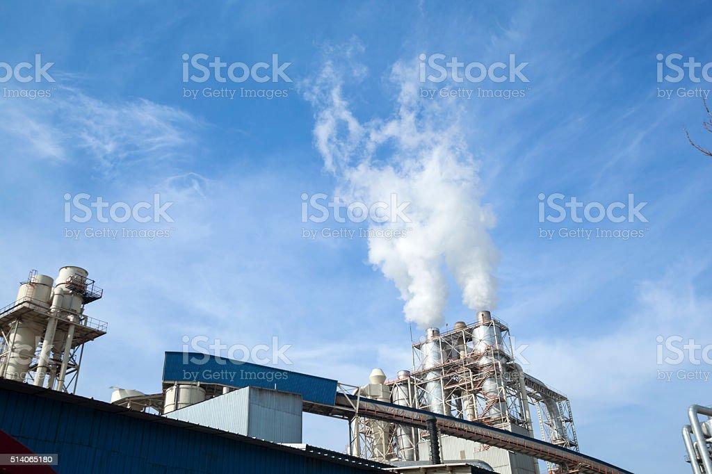 Industrielle de fumée de cheminée sur du ciel bleu - Photo