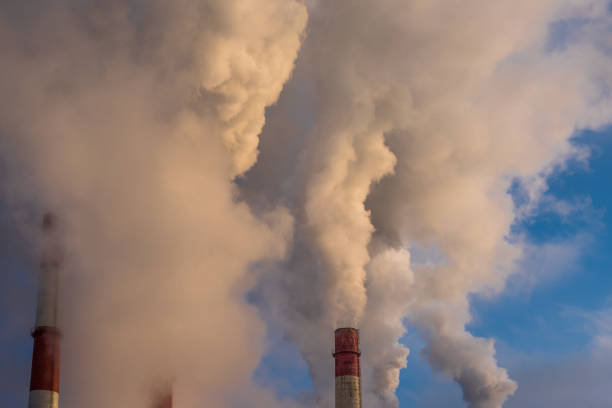 industrial smoke from chimneys on blue sky stock photo