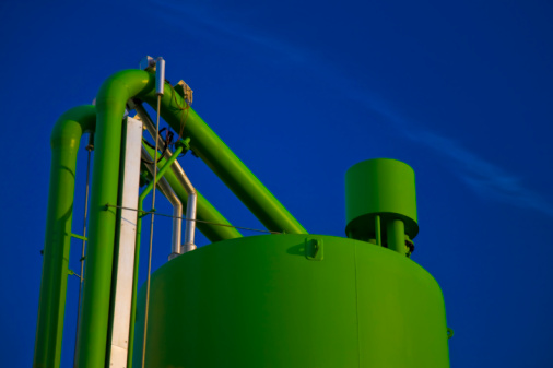 industrial storage tank and pipes against blue sky