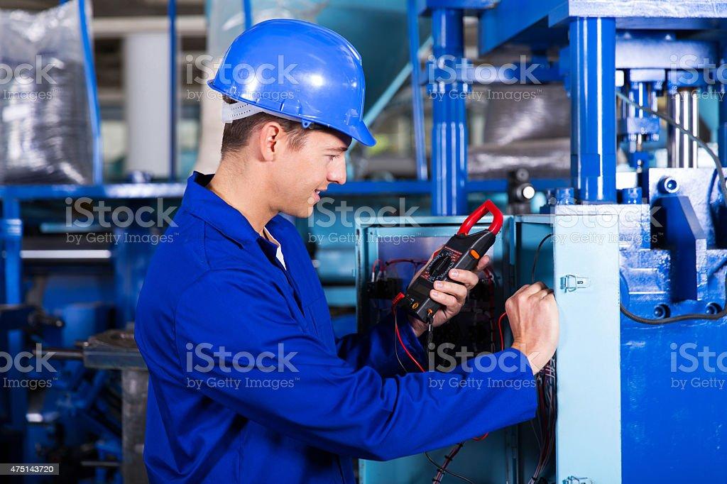 industrial technician examining control box stock photo