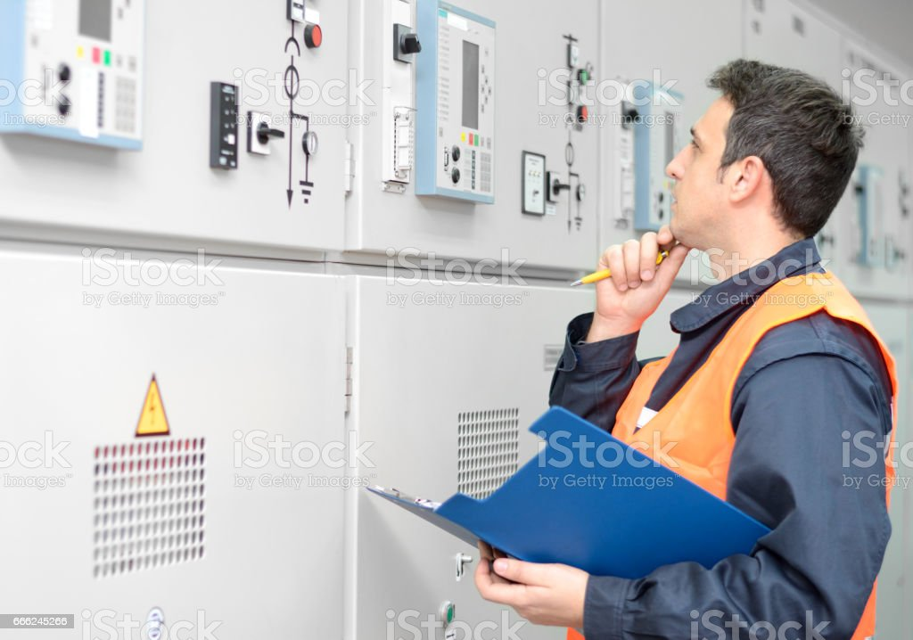 Industrial technician operating in electricity substation stock photo