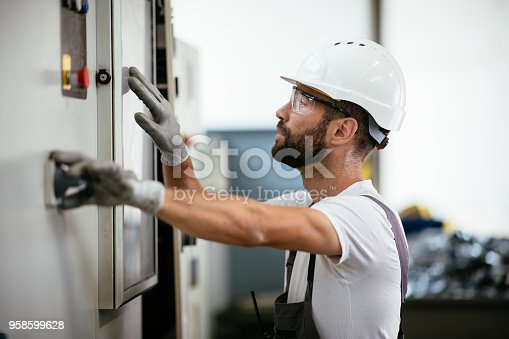 Industrial technician operating in electricity substation. Shallow DOF. Developed from RAW; retouched with special care and attention; Small amount of grain added for best final impression. 16 bit Adobe RGB color profile.
