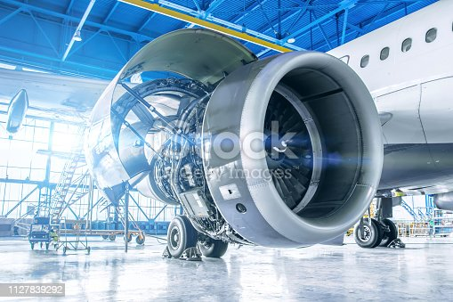 istock Industrial theme view. Repair and maintenance of aircraft engine on the wing of the aircraft. 1127839292
