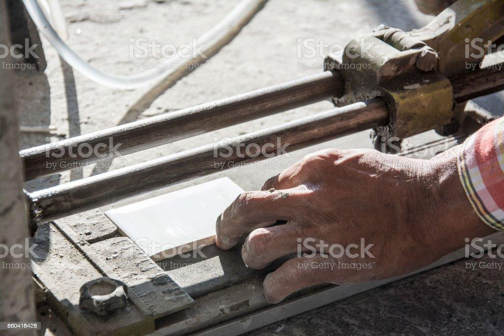 industrial tiler builder worker working with floor tile cutting equipment stock photo