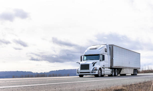 Industrial transportation big rig white semi truck transporting frozen cargo in reefer semi trailer running on the road with cloudy sky stock photo