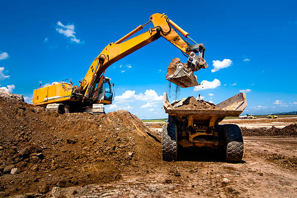 Industrial truck loader excavator moving earth and unloading int stock photo