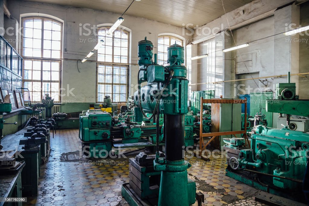 Industrial turning and drilling machine tools in old workshop.