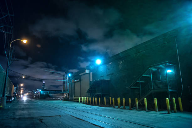 Industrial urban street city night scene with vintage factory warehouses and train tracks stock photo