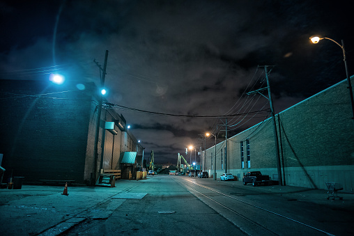 Industrial urban street city night scene with vintage factory warehouses and train tracks