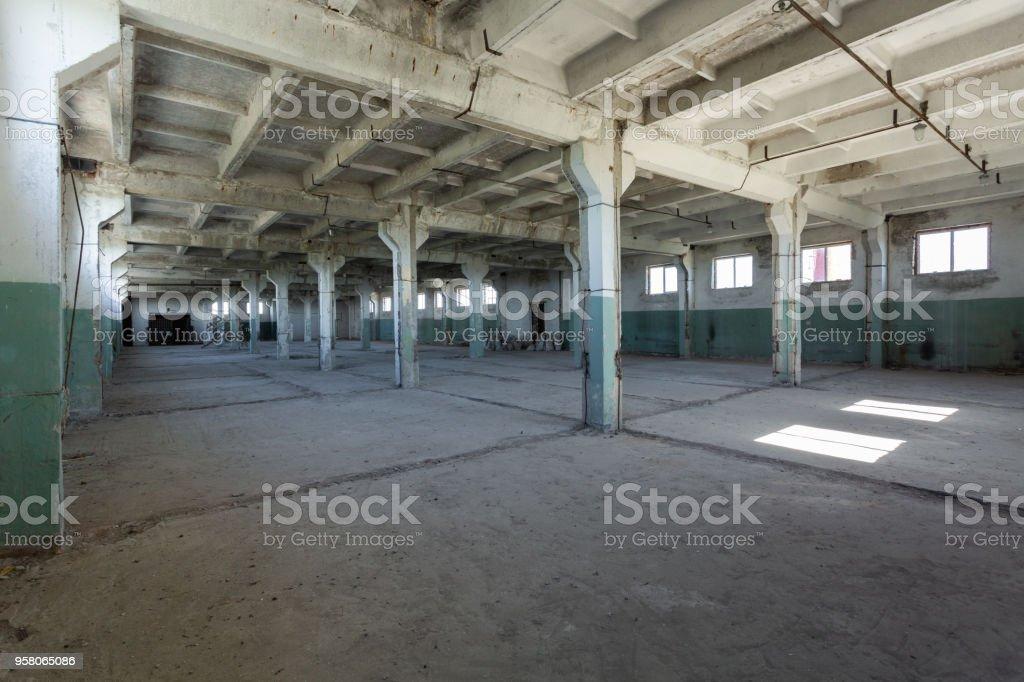 Industriehalle mit Zement-Mauern, Fußböden, Fenster und Säulen vor dem Bau, Umbau, Renovierung, Erweiterung, Sanierung, Umbau. Industrieerfahrung. – Foto