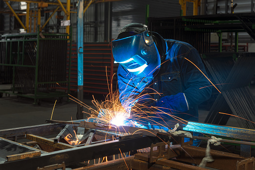 Close-up of a Industrial Welder holding welding Torch with welding sparks.