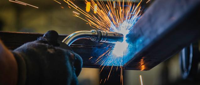 Industrial Welder With Torch in big hall welding metal profiles