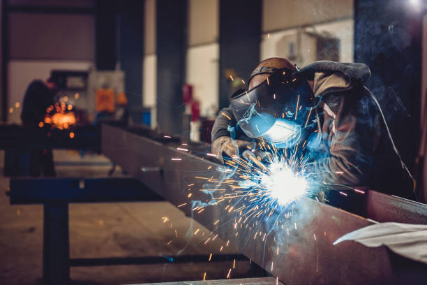 Industrial Welder With Torch Industrial Welder With Torch and Protective Helmet in big hall welding metal profiles manufacturing stock pictures, royalty-free photos & images