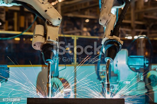 istock Industrial welding robots in production line manufacturer factory 672453858