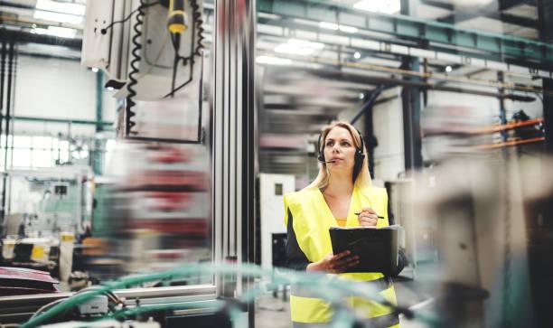 industrielle frau ingenieur mit kopfhörer in einer fabrik arbeiten. kopieren sie raum. - weibliche führungskraft stock-fotos und bilder