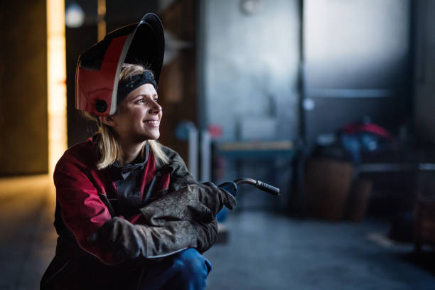 Industrial woman worker at the welding factory. stock photo