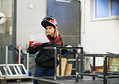 Industrial young woman worker at the welding factory.