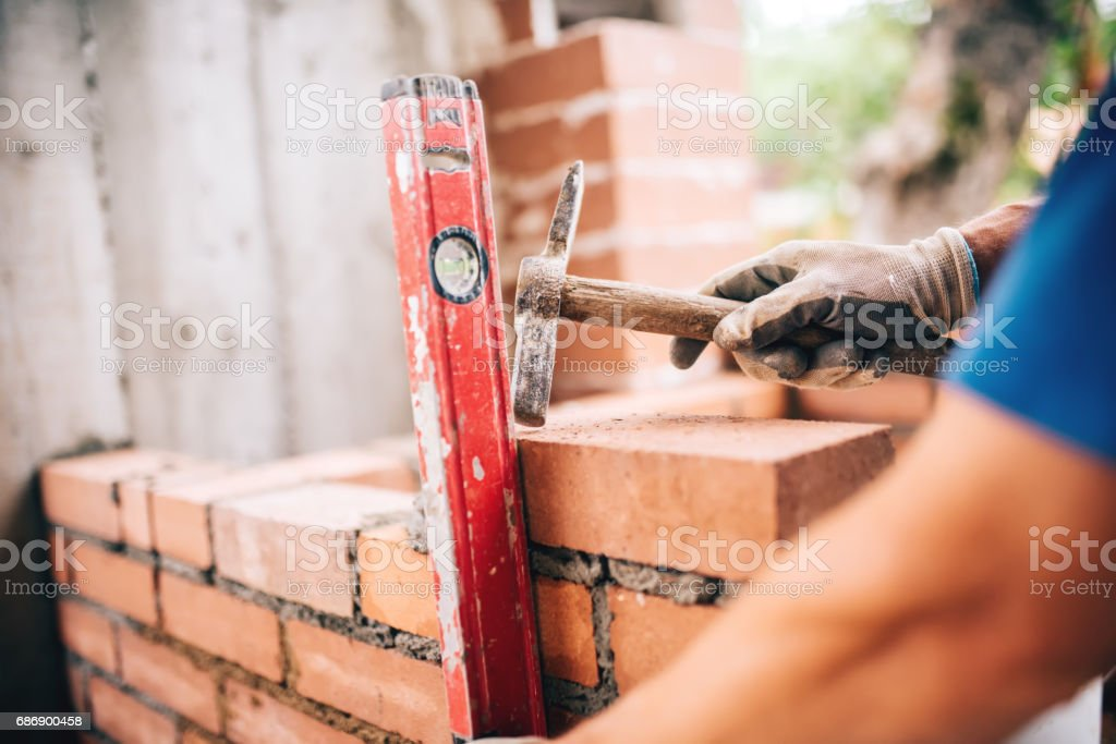 industrial worker building exterior walls, using hammer and level for laying bricks in cement. Detail of worker with tools stock photo