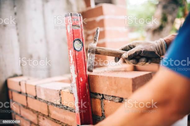 Industriearbeiter Gebäude Außenwände Mit Hammer Und Ebene Für Die Verlegung Von Steinen In Zement Detail Des Arbeitnehmers Mit Werkzeugen Stockfoto und mehr Bilder von Steinmetz