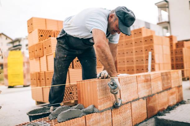 operaio industriale che costruisce pareti esterne, utilizzando martello per la posa di mattoni in cemento. dettaglio del lavoratore con utensili e calcestruzzo - costruire foto e immagini stock