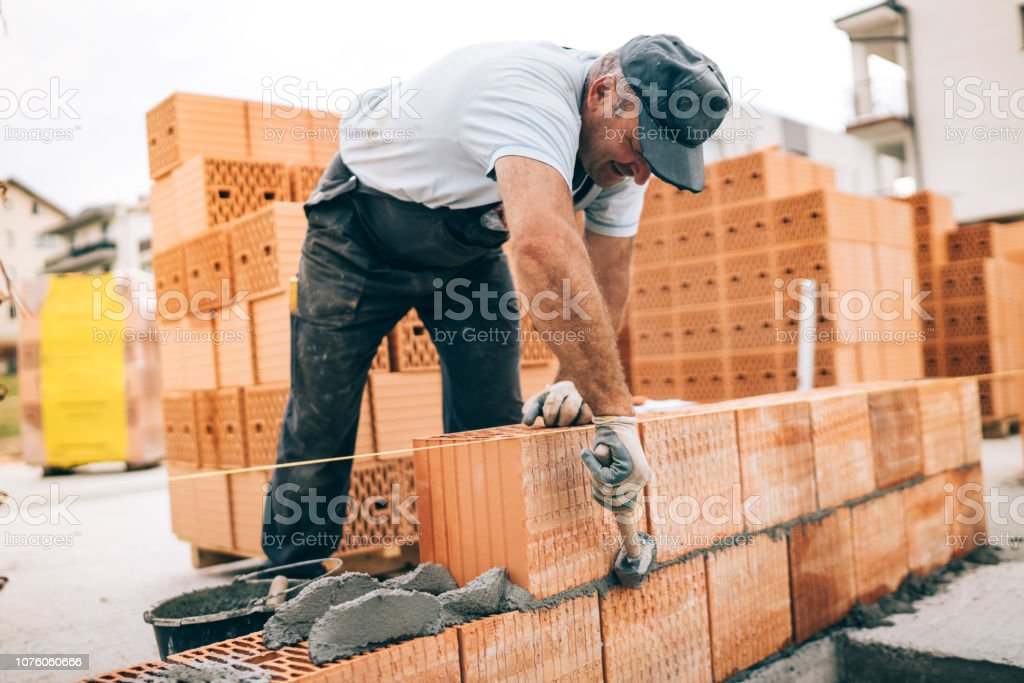 industrial worker building exterior walls, using hammer for laying bricks in cement. Detail of worker with tools and concrete stock photo