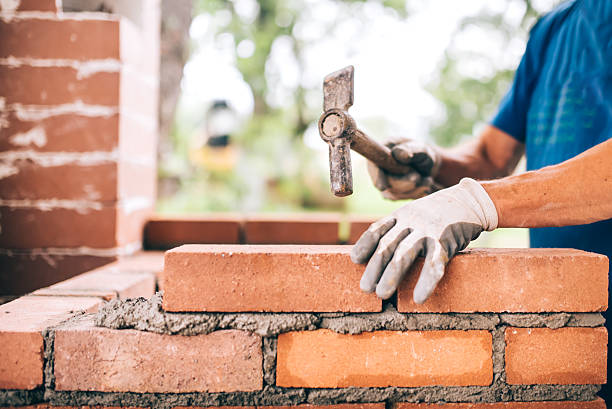 industrial worker building exterior walls, using hammer for laying bricks stock photo