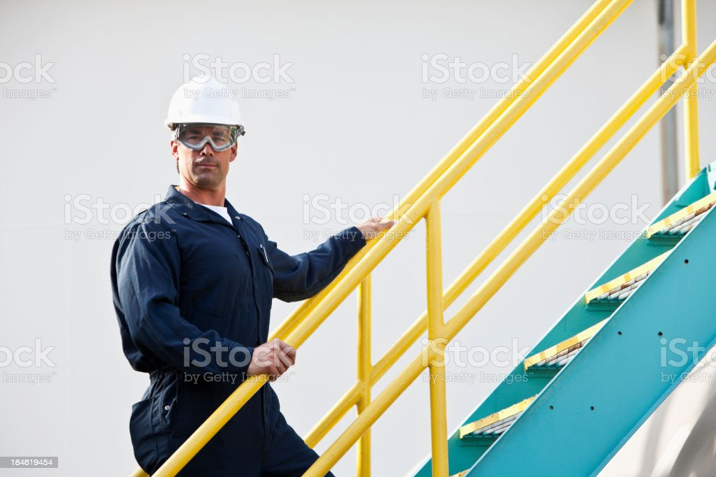 Industrial worker climbing metal staircase stock photo
