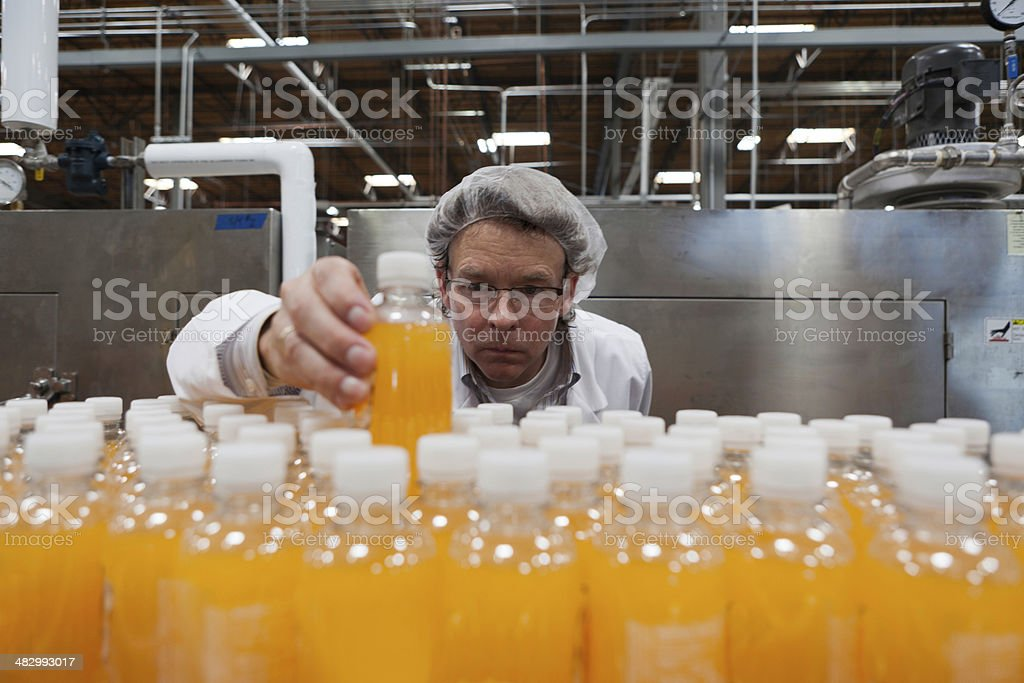 Industrial worker examining bottle in factory stock photo