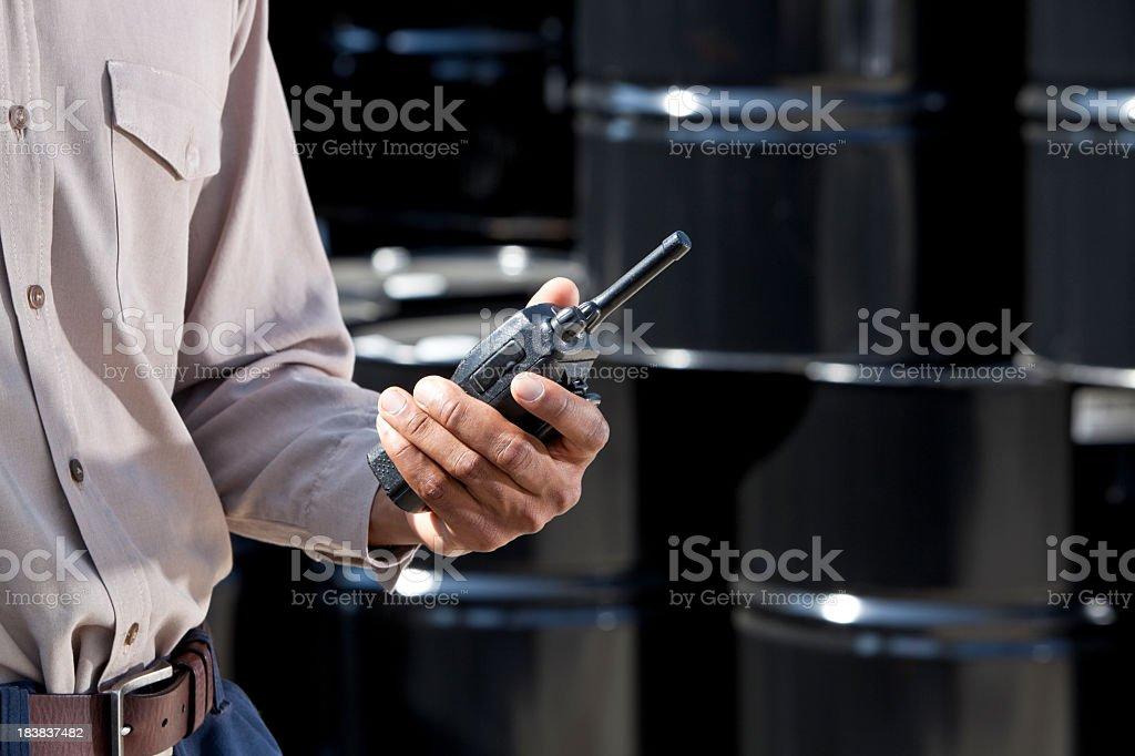 Industrial worker holding walkie talkie by steel drums stock photo