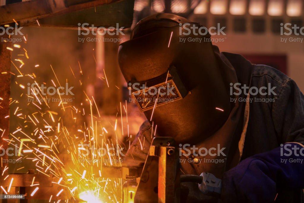 Industrial worker is welding in automotive part factory stock photo
