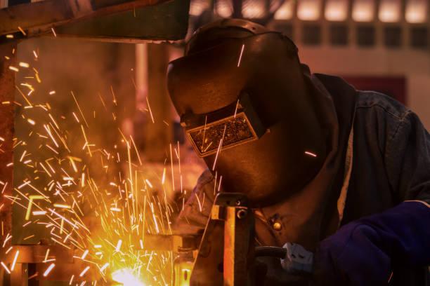 industriearbeiter schweißt in automotive teilefamilie - bogen bauen stock-fotos und bilder