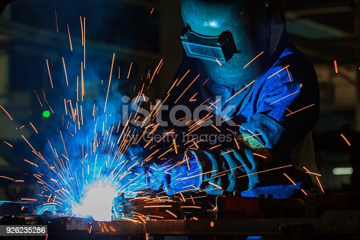 istock Industrial worker is welding metal part in factory 926235286