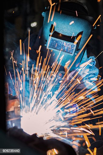 istock Industrial worker is welding metal part in factory 926235440