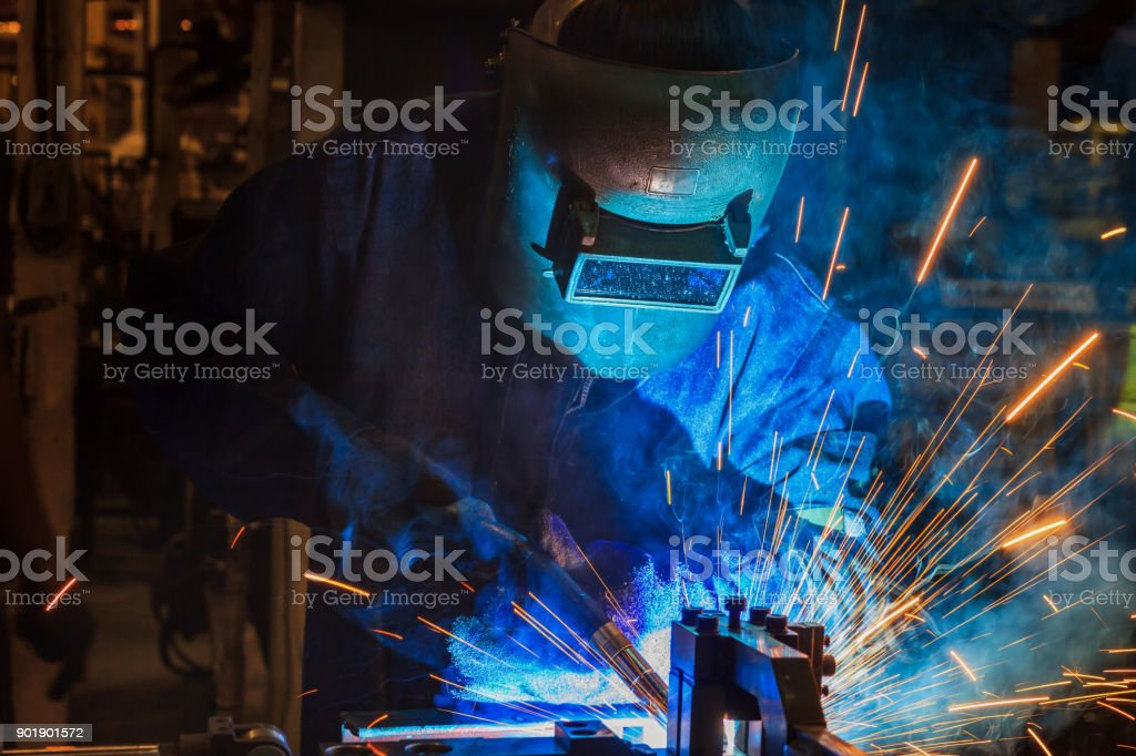 Industrial worker is welding repair metal part in car factory stock photo