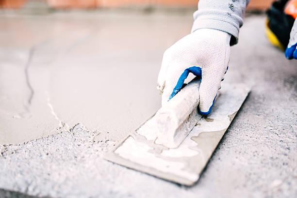 operaio industriale in cantiere posa sigillante per impermeabilizzazione cemento - calcestruzzo foto e immagini stock