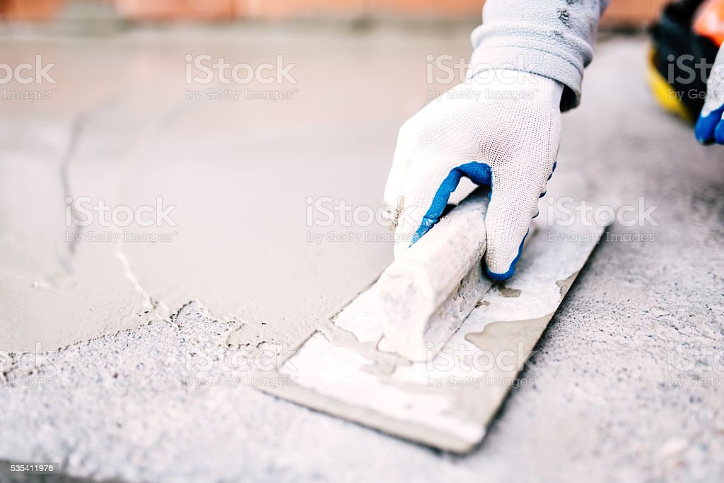 industrial worker on construction site laying sealant for waterproofing cement stock photo