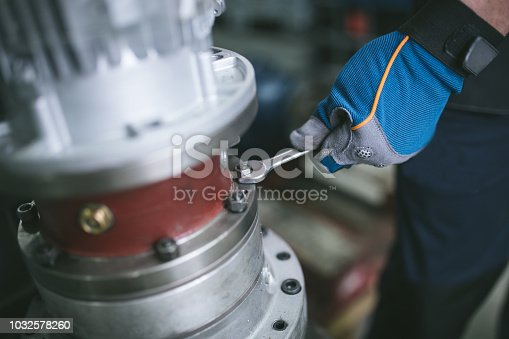 Industrial worker hand with protective gloves taking a spanner.