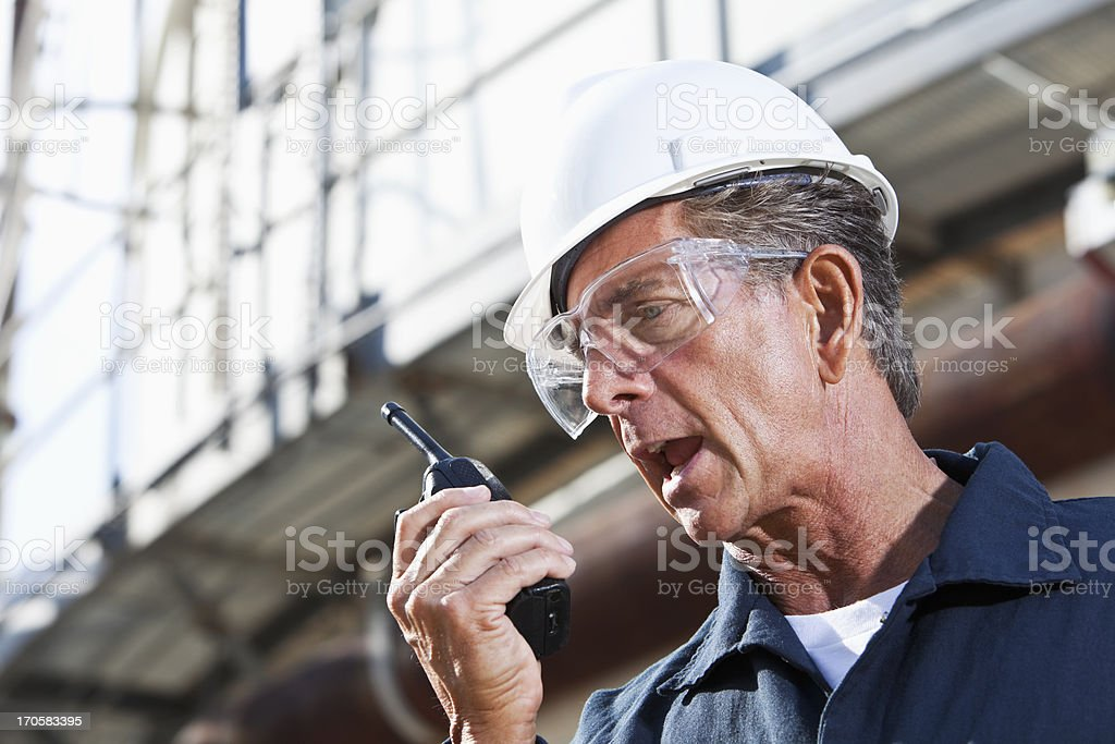 Industrial worker talking into walkie-talkie royalty-free stock photo