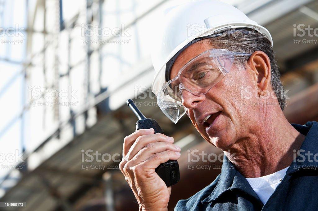 Industrial worker talking into walkie-talkie stock photo