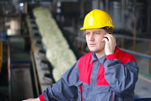 industrial worker talking on cell phone - zuccherificio foto e immagini stock