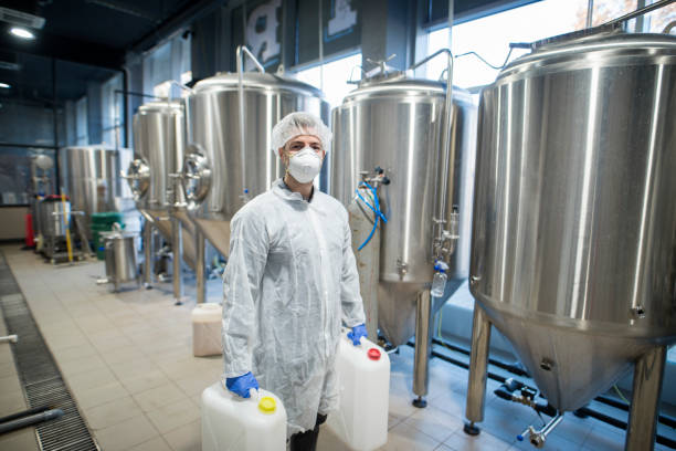 Industrial worker technologist in white protective suit with hairnet and mask holding plastic cans with chemicals in food factory production line. Industrial worker technologist in white protective suit with hairnet and mask holding plastic cans with chemicals in food factory production line. chemical plant stock pictures, royalty-free photos & images