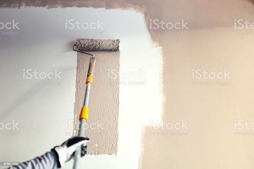 industrial worker using roller and other tools for painting walls royalty-free stock photo