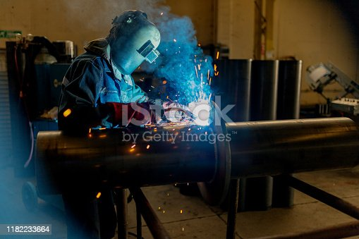 Industrial worker welding on the pipe
